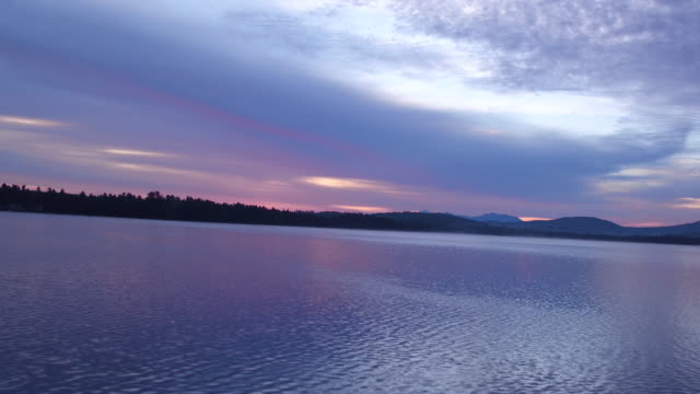 Aerial flying over water of Saranac lake past small island at Sunrise