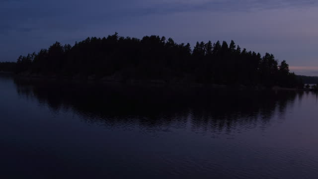 Aerial flying over water of Saranac Lake towards the shore and past a small island, sunrise