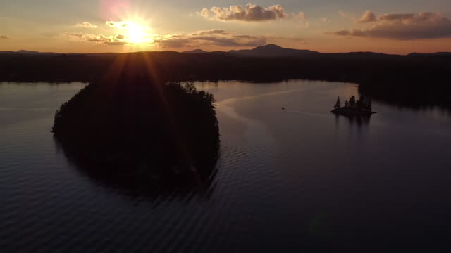 Aerial flying over water of Saranac lake towards then over small island at sunset