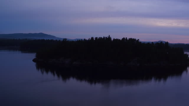 Aerial flying over water of Saranac lake towards then over small island at sunrise