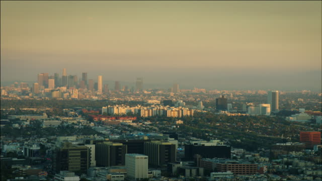 aerial pov flying over west hollywood, looking at cedars-sinai medical center, and the beverly center, past park la brea, to see downtown los angeles, ca in the distance, at sunset. - west hollywood stock videos and b-roll footage