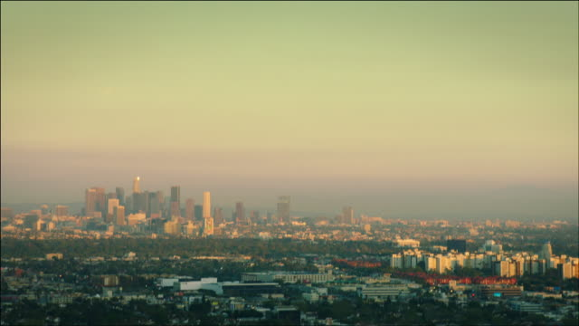 vídeos y material grabado en eventos de stock de aerial pov flying over west hollywood, looking past southern hollywood, to see downtown los angeles, ca in the distance, at sunset. - west hollywood