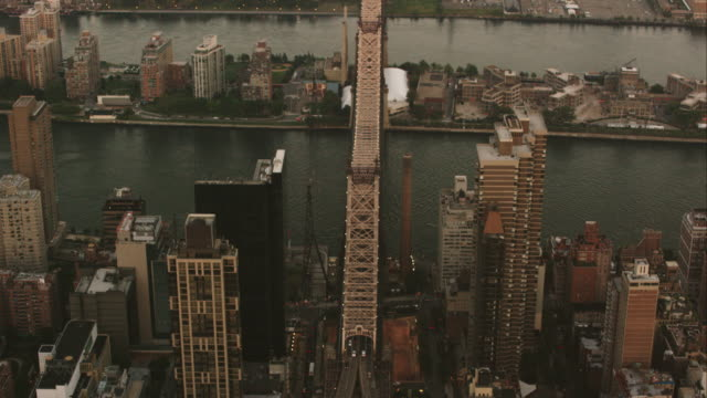 aerial flying over west side of manhattan looing east at queensboro bridge, sunset in nyc - queensboro bridge stock videos & royalty-free footage