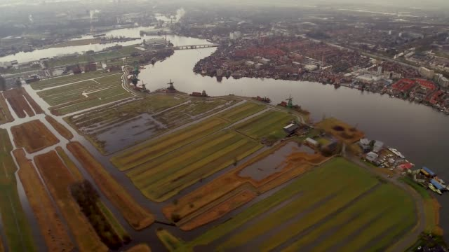 aerial flying over windmills of zaans schans north of amsterdam, netherlands daytime - netherlands stock videos & royalty-free footage