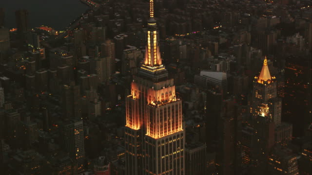 Aerial flying past Empire State Building twinkling yellow then changing color, NYC