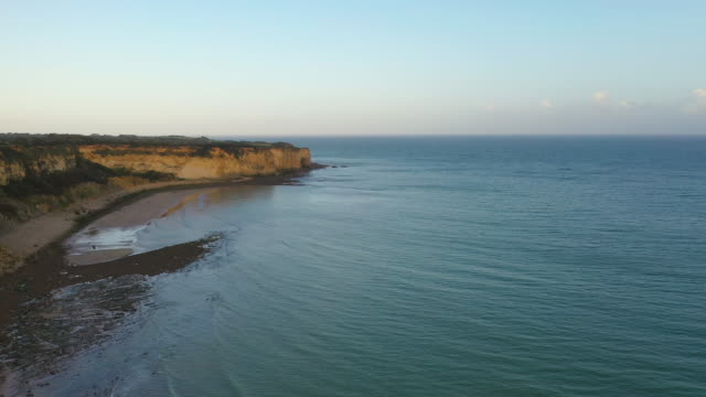 aerial flying past the cliffs of omaha beach in france at sunrise - normandy stock videos & royalty-free footage