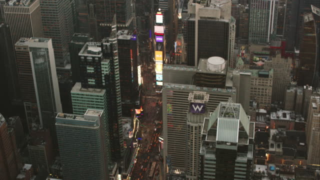 aerial flying south on broadway looking down at times square with lights on in nyc - electronic billboard stock videos and b-roll footage