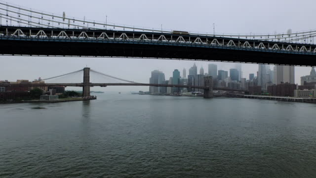 aerial flying south under the manhattan and brooklyn bridges on the east river, nyc - brooklyn bridge stock videos & royalty-free footage