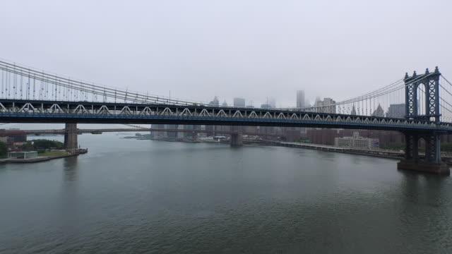 vídeos y material grabado en eventos de stock de aerial flying south under the manhattan bridge on the east river, nyc - manhattan bridge