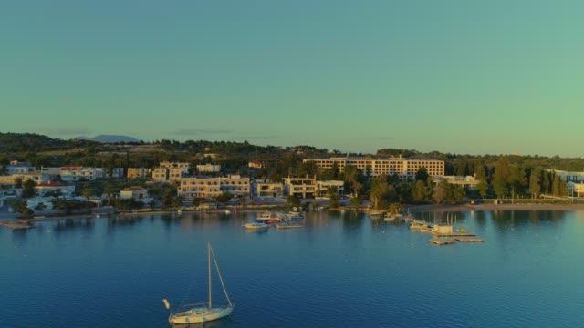 Aerial - flying straight forward above a small harbor at dusk - Porto Heli - Porto Cheli - Greece - Argolis - Argolida