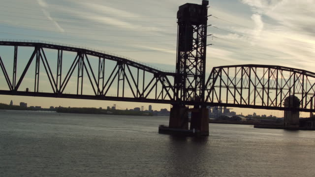 aerial flying toward railroad bridge with philadelphia skyline in the distance - デラウェア川点の映像素材/bロール