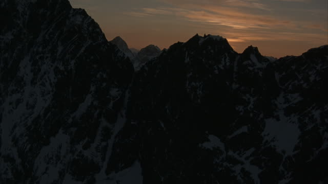 Aerial flying towards a gap between two rugged mountain peaks during golden hour.
