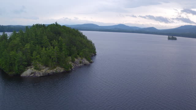 Aerial flying towards and around small island on Saranac lake, late afternoon
