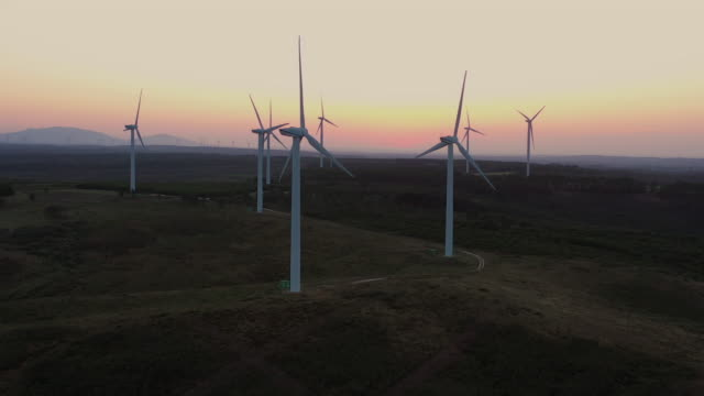 aerial flying towards and close to cluster of windmills, wind farm in southern portugal at sunrise - turbine stock-videos und b-roll-filmmaterial