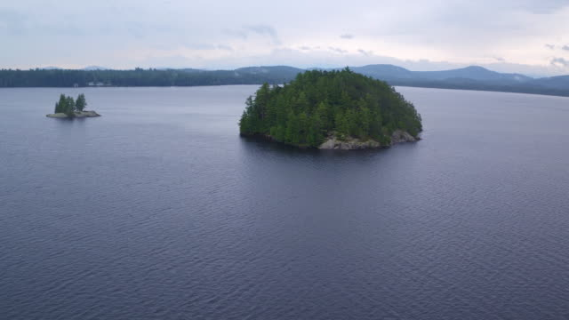 Aerial flying towards and over small island on Saranac lake, late afternoon