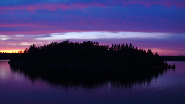 Aerial flying towards and over small island on Saranac lake, sunset