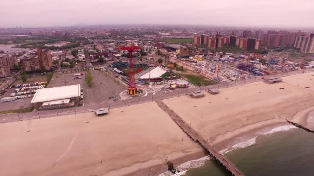 aerial flying towards coney island and beach over atlantic ocean in brooklyn, new york city - boardwalk stock videos & royalty-free footage