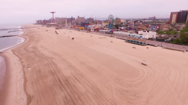 aerial flying towards coney island, over the ocean in brooklyn, new york city - coney island stock-videos und b-roll-filmmaterial
