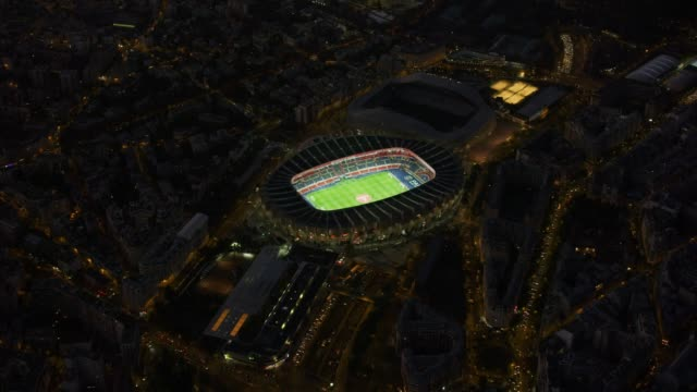 aerial flying towards soccer stadium with lights on in paris france, night - stadium stock videos & royalty-free footage