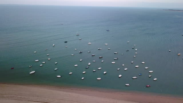 aerial flying towards the ocean of ile de re with boats anchored, france at sunrise - anchored stock videos & royalty-free footage