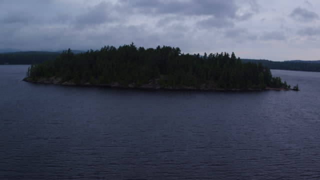 Aerial flying towards then over small island in Saranac lake, afternoon