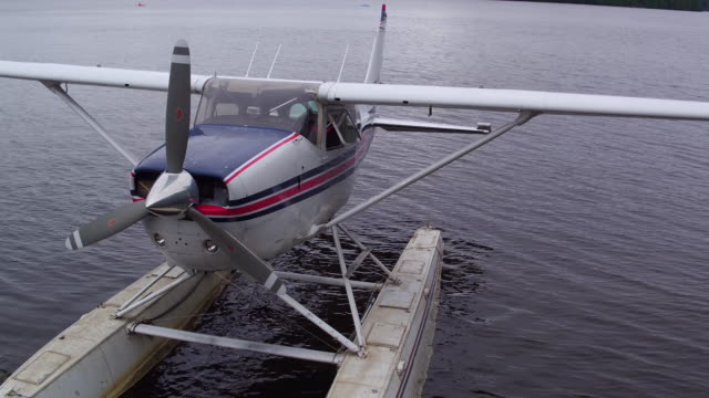 Aerial flying up from view of docked seaplane in Saranac lake