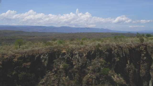 Aerial WS flying up over Rift Valley escarpment then low over bush