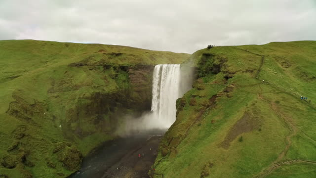 Aerial flying up over Skógafoss waterfall tilting down on river as camera fly's up in Iceland