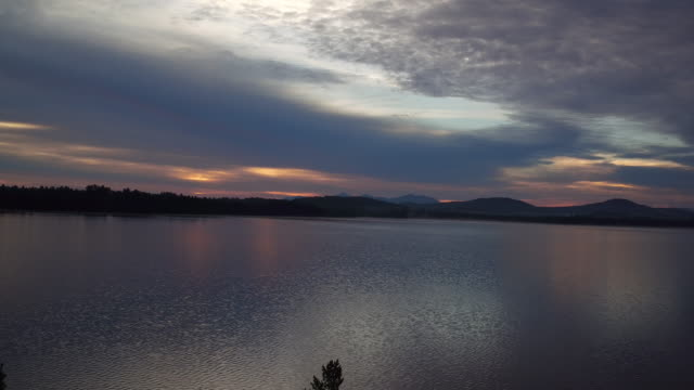 Aerial flying up over water of Saranac lake at Sunrise