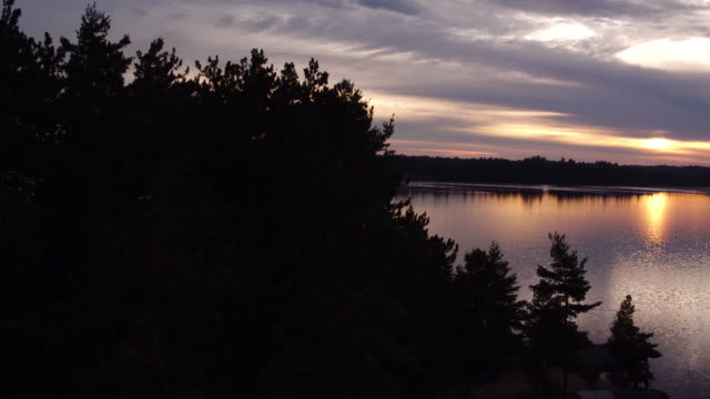 Aerial flying up was evergreen trees over water of Saranac lake at sunset