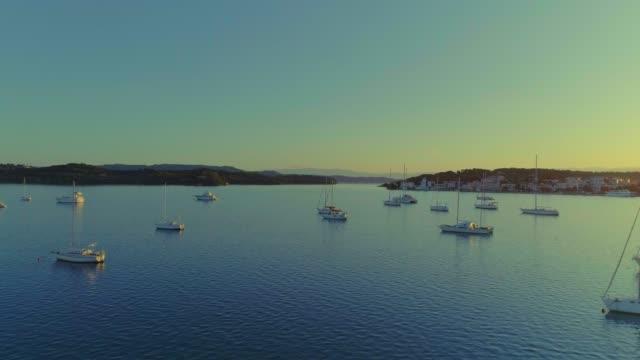 Aerial - flying upwards above a small harbor at dusk - Porto Heli - Porto Cheli - Greece - Argolis - Argolida