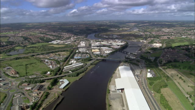 Aerial flying west over River Tyne / over highways and warehouses / Northumberland, England