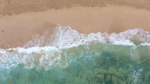 aerial flyover along pristine beach and surf on kauai, hawaii - isola di kauai video stock e b–roll
