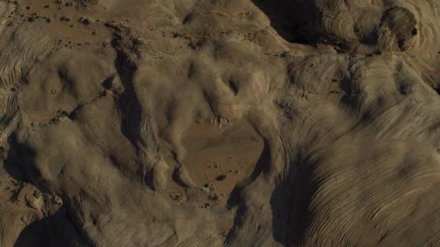 vídeos y material grabado en eventos de stock de aerial flyover directly above brown desert landscape / glen canyon national park, utah, united states - marrón