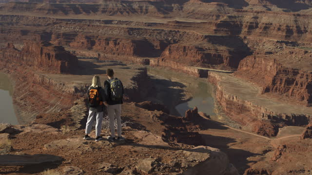 aerial flyover of hikers at desert overlook photographing river basin / moab, utah, united states - moab utah stock-videos und b-roll-filmmaterial