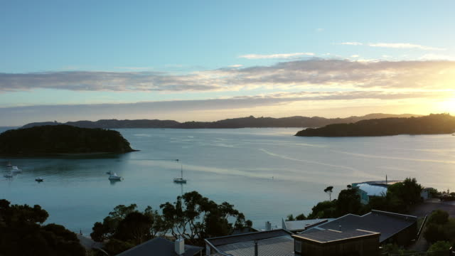 aerial flyover view of boats in ocean near waterfront / paihia, new zealand - bay of islands new zealand stock videos & royalty-free footage