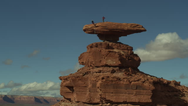 aerial flyover view of people rappelling from top of hat rock / mexican hat, utah, united states - abseiling stock videos & royalty-free footage