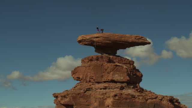 aerial flyover view of people standing on top of hat rock / mexican hat, utah, united states - balance stock videos & royalty-free footage