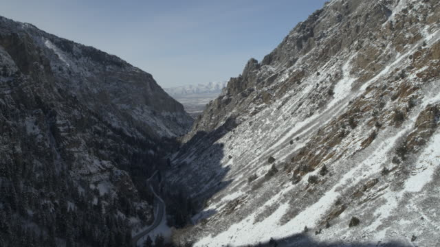 aerial flyover view of remote winding road in valley during winter / american fork canyon, utah, united states - american fork canyon stock videos and b-roll footage