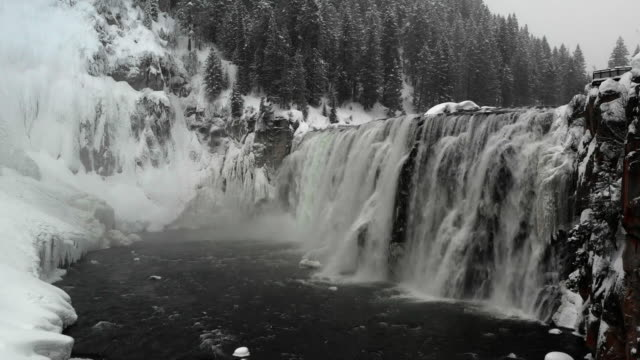 aerial flyover view of river and waterfall in winter near trees / island park, idaho, united states - ingrandimento video stock e b–roll