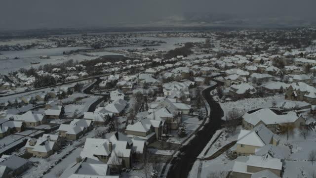 Aerial flyover view of suburban neighborhood houses in winter / Cedar Hills, Utah, United States