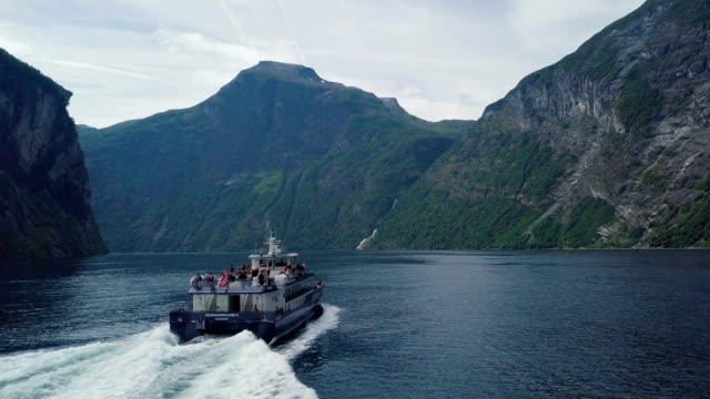 aerial / following a cruise boat in geirangerfjord , norway - norvegia video stock e b–roll