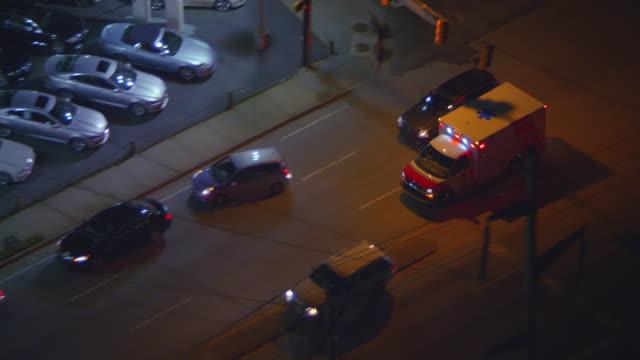 vídeos y material grabado en eventos de stock de aerial following ambulance, nd city street, night - ambulancia