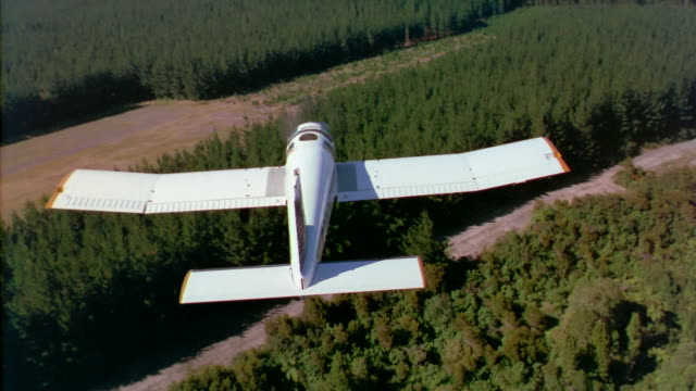 stockvideo's en b-roll-footage met aerial following behind crop duster spraying pines of ashley forest/ ashley, canterbury, new zealand - insecticide