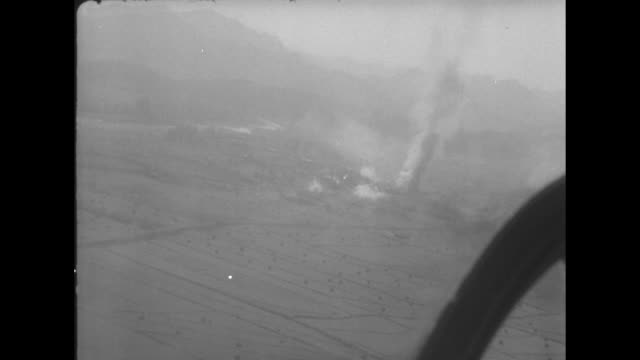 aerial POV following F51 as it flies / POV from inside helicopter at explosions and smoke on ground helicopter frame at right / POV from inside...