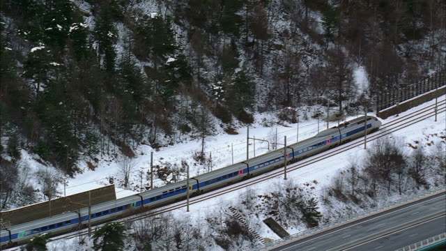 aerial following passenger train in and out of tunnels through swiss alps / switzerland - passenger train stock videos & royalty-free footage