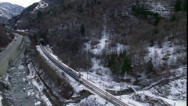 aerial following passenger train through tunnels in alps and alongside highway / switzerland - passenger train stock videos & royalty-free footage
