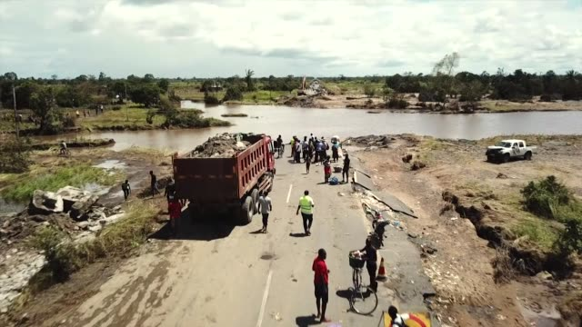 vídeos de stock e filmes b-roll de aerial following road that disappears into flood water following cyclone idai in mozambique - moçambique