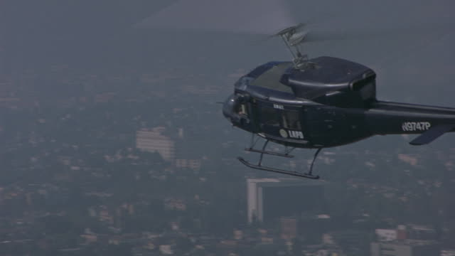 Aerial following-shot of a black LAPD helicopter flying low over the city on a smoggy day.