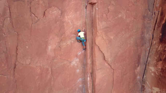 Aerial follows rock climber as he ascends sandstone rock face on Moab climbing expedition.